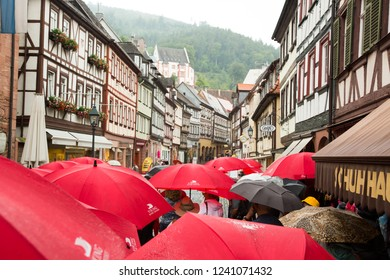 Miltenberg, Germany - 7/4/2013:  A tour group walking in the rain on a main street in Miltenberg, Bavaria, Germany