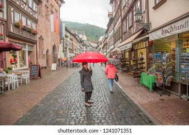 Miltenberg, Germany - 7/4/2013:  A woman tourist walking in the rain down a main street in Miltenberg, Bavaria, Germany