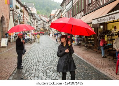 Miltenberg, Germany - 7/4/2013:  A woman tourist walking in the rain down a main street in Miltenberg, Bavaria, Germany