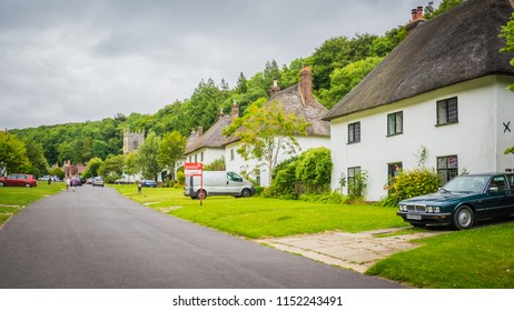 Milton Abbas, Dorset / UK - 07 11 2017: Old Medieval English village in the southwest of the UK. Street with old thatched houses in England.