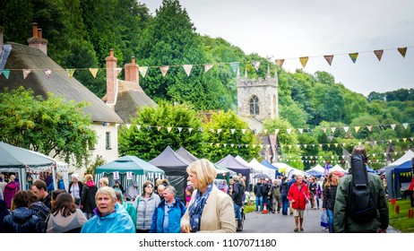 Milton Abbas / UK - July 29 2017: People are walking down the street in Milton Abbas village, Dorset during the 18th-century? street fair. English traditional medieval fair / market countryside.