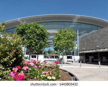 Milton Keynes, Buckinghamshire, England-July 5th 2019: Milton Keynes central shopping mall, seen from Midsummer Boulevard in summer sunshine with trees and flower beds in bloom.