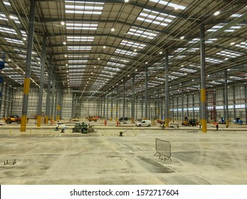 Milton Keynes,  Buckinghamshire /UK - 26 November 2019: Steel Construction Interior of a Warehouse with Construction Equipment and Workmen laying a New Concrete Floor Section.
