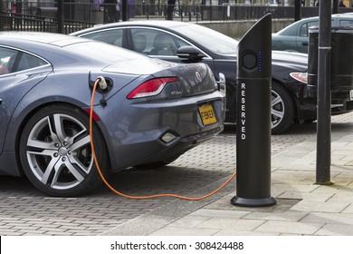 MILTON KEYNES, ENGLAND - MARCH 5, 2015: Modern electric car charging at station dock point near parking lot, United Kingdom