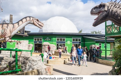 Milton Keynes, England, UK - September 2018: Gulliver's Dinosaur & Farm Park, Lost World - Milton Keynes, UK. Entrance of the park with people visiting and big dinosaurs replicas