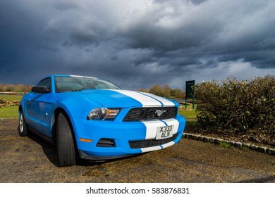MILTON KEYNES, UK - 14 FEBRUARY 2017: Ford Mustang tuning sport-car colored in blue color with white stripes - focus on headlights. Editorial photo