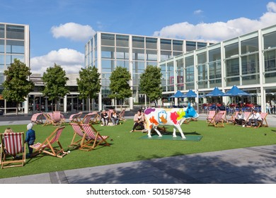 Milton Keynes, United Kingdom - October 4, 2016: People sitting in deckchairs in the courtyard of Milton Keynes largest shopping centre, MK Centre.