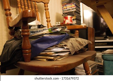 Milwaukee, WI / USA - May 3, 2020: A hoarder piles old newspapers, books, DVDs and other unimportant items on a rocking chair that has become unusable in the living room.