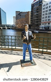 Milwaukee, Wisconsin - May 26th, 2018:  The infamous Bronze Fonz statue of Henry Winkler from Happy Days TV show designed by Gerald P. Sawyer stands alone on the Milwaukee river on a warm spring day.