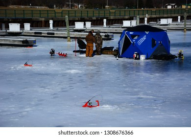 Milwaukee, Wisconsin / USA - February 9, 2019: Ice fishing in the Milwaukee marina on a calm cold afternoon.