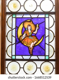Milwaukee, Wisconsin / USA - Jan 11, 2020: Stained glass within the miller guest house with different depictions of people with beer. Miller girl sitting on the moon