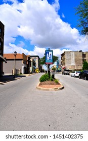 Milwaukee, Wisconsin / USA - July 11, 2019:  Looking west down the road along the Historic Mitchell Street district on a beautiful blue sky and clouded day.