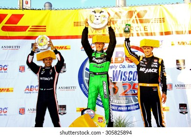 Milwaukee Wisconsin, USA - July 12, 2015: Verizon Indycar Series Milwaukee Mile. Victory Circle Podium - Helio Castroneves, Sebastien Bourdais, Graham Rahal wear cheese heads, cheese awards held high.