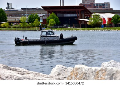Milwaukee, Wisconsin / USA - June 3, 2019:  Milwaukee Police in their patrol boat cruise the waterfront in front of the Summerfest grounds on a clear spring day.
