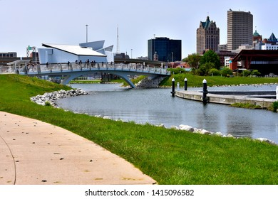 Milwaukee, Wisconsin / USA - June 3, 2019:  A bridge in Wisconsin's Lakeshore State Park is being used by schoolchildren on a warm spring afternoon as they tour the park with the skyscrapers behind.
