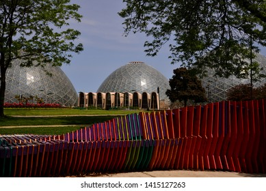 Milwaukee, Wisconsin / USA - June 3, 2019: The Mitchell Park Domes with a lightly clouded sky in the background and framed with trees and color in the foreground.