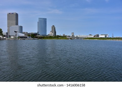 Milwaukee, Wisconsin / USA - June 3, 2019: The Milwaukee skyline as seen from Lakeshore State Park across from the Summerfest Grounds and Discovery World in the distance.