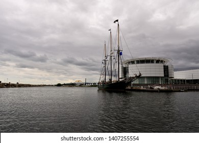 Milwaukee, Wisconsin / USA - May 25, 2019:  The tall ship in front of the museum in the harbor of Lake Michigan with stormy clouds and the Hoan Bridge in the background.