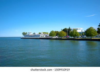 Milwaukee, Wisconsin / USA - September 18, 2019: Landscape view of Lake Michigan in Milwaukee, Wisconsin with Harbor Restaurant in distance on a summer day.