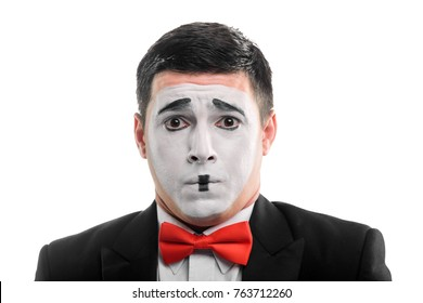 Mime artist imitates anxiety. Close view on a man in a suit and a red bow tie, make-up on his face to exaggerate emotions.