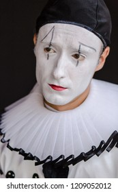 Mime artist on black background. Mime performer with white face make up. Black and white costume. Big black buttons. Hanged doll. Mimicking emotions. Model is a professional mime artist. Studio shot.