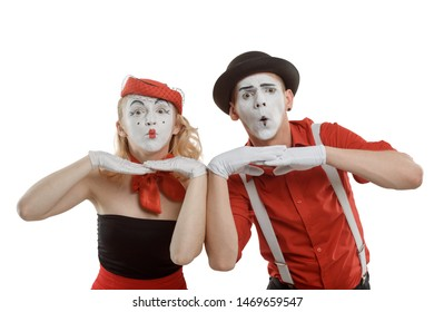 Mime artists spying over an imaginary fence on white. Curiosity and surprised faces, revealing the truth.