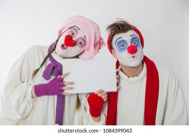 mime boy and mime girl holding a white nameplate. Human emotions. Clowns on holiday.