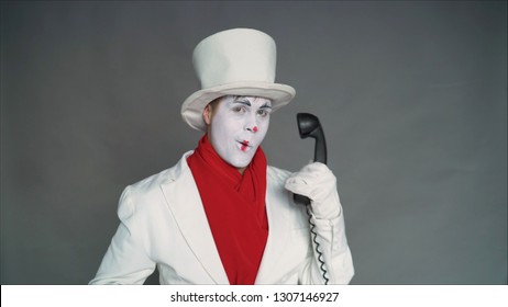 Mime calls by phone. Mime with an old pipe. boy-mime with the phone. Human emotions. Clown talking on the phone.