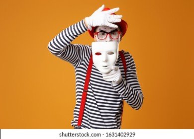 Mime clown in red hat and in vest with white mask on orange background