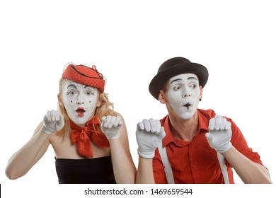 Mime couple spying over a fence, isolated on white. Funny pantomime performance with imaginary objects, illusion.