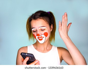 mime girl in white t-shirt with mobile phone in hand. Man with emotions on a white background. Surprised creepy, funny clown girl using smartphone isolated over gray