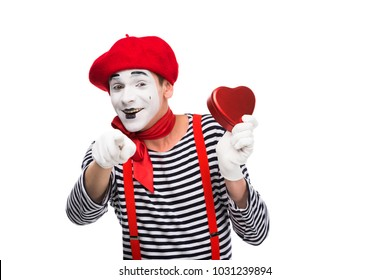 mime holding heart shaped gift box and pointing on camera isolated on white, st valentines day concept
