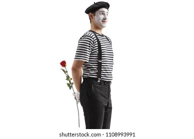 Mime holding a rose flower behind his back isolated on white background