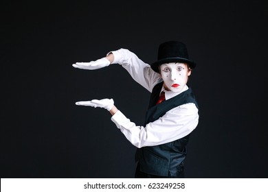 Mime holds his palms parallel in the air
