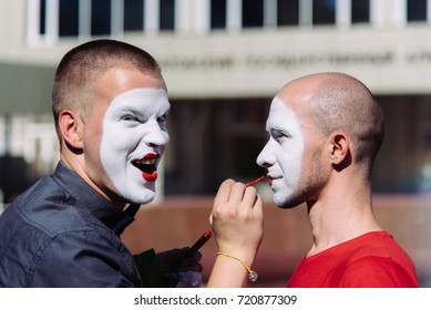 mime makes make-up for his partner on the street