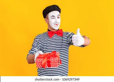 Mime man holding gift box, showing like sign and wink. Emotions and feelings concept. Indoor shot, yellow background