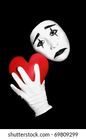 Mime with red heart. Actor mime with black and white make-up holding red heart in the hand. Isolated on black background.