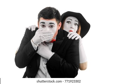 Mimes imitate fear and anxiety. Man covering his mouth and woman, standing behind him, are afraid of something scary.