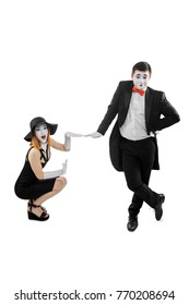 Mimes leaning on invisible box. Funny dumb show, performed by duo of woman and man, dressed in 20's style clothing. Isolated on white.