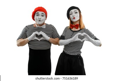 Mimes making a heart shape with their hands. Man and woman, dressed in scenic costume, are showing love sign and pursing lips to imitate kiss.
