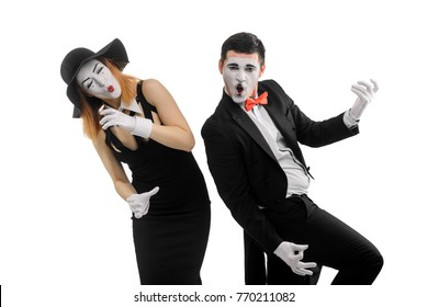 Mimes playing music instruments. Duo of female and male actors, dressed in old-fashioned style, performing a dumb show and holding imaginary objects.
