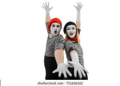 Mimes standing back to back. Waist up portrait of male and female mime artists in standard striped clothing, wearing special make-up to exaggerate emotions.