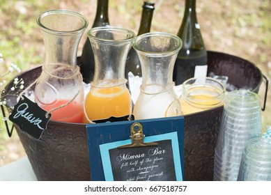 A mimosa bar with a selection of fresh fruit juices and prosecco at an outdoor party.