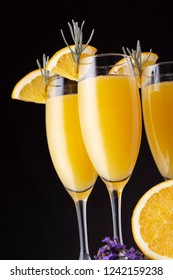 Mimosa cocktails in champagne glasses with orange juice and sparkling wine decorated with lavender leaves and orange slices. Focus on the lavender leaves on the glass