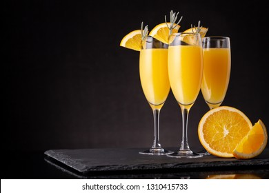 Mimosa cocktails in champagne glasses with orange juice and sparkling wine decorated with lavender leaves and orange slices