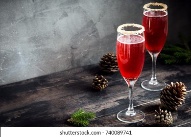 Mimosa festive drink for Christmas - champagne red cocktail Mimosa with cranberry for Christmas party, copy space