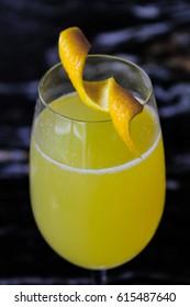 A mimosa or yellow/orange cocktail with an orange or lemon peel garnish.