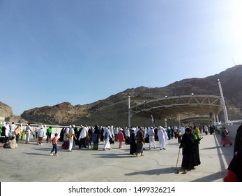 MINA, SAUDI ARABIA-AUGUST 12, 2019 :  A group pilgrims from complete their  'stoning the devil' ritual at the three jamrah (place of pebbles) in the background.This ritual is part of the hajj process.