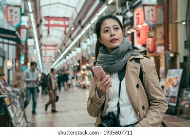 Minami Namba and Shinsaibashi. female tourist standing in local market and searching fresh seafood shop at daytime. young girl carrying camera and holding smartphone look japanese local lifestyle