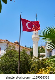 Minaret of Kelerlik Mahallesi Cami mosque with the official flag of the Republic of Turkey waving in foreground. Bodrum. Mugla Province, Turkey.